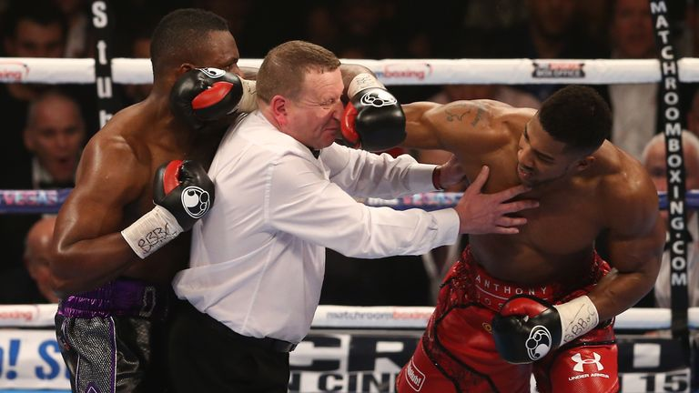 TOPSHOT - Referee Howard Foster (C) tries to separate British boxer Dillian Whyte (L) and British boxer Anthony Joshua (R) after the bell had rang in round