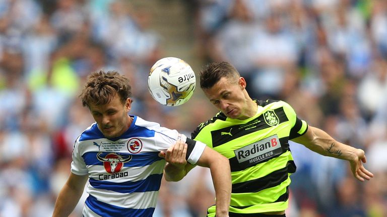 Reading's John Swift of Reading and Jonathan Hogg of Huddersfield Town battle to win the ball
