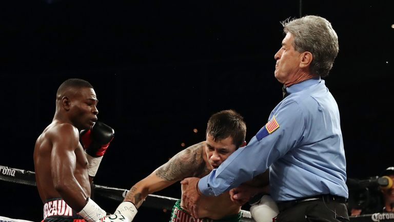 Flores topples into the arms of referee Vic Drakulich at the end of the first round