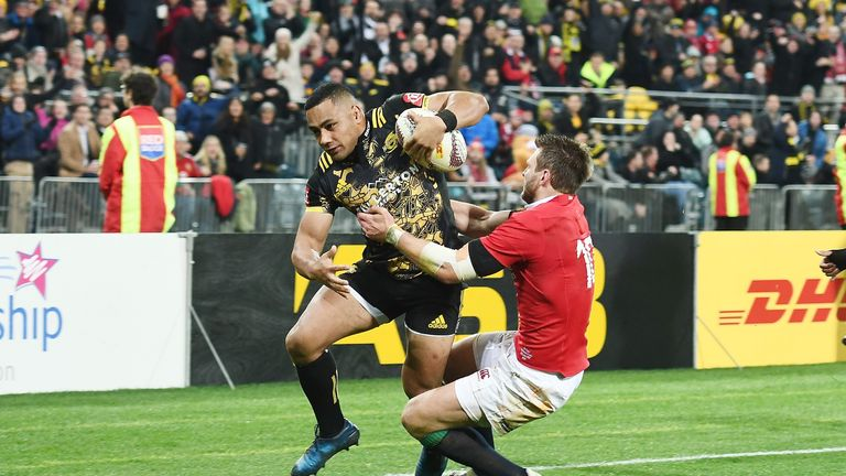 Ngani Laumape of the Hurricanes breaks a tackle by Dan Biggar
