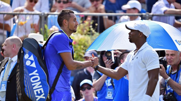 Nick Kyrgios (L) shakes hands with Donald Young of the US after having to retire