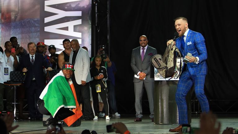 Mayweather is draped in an Irish flag while McGregor goes through his bag