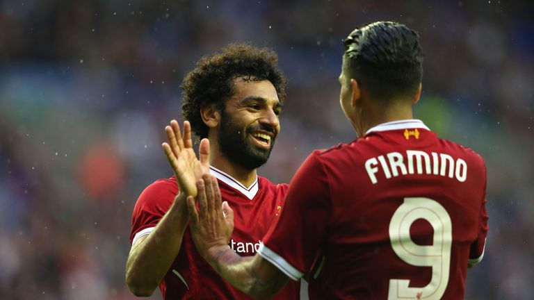 Liverpool's Mohamed Salah celebrates with Roberto Firmino after scoring their first goal during a pre-season friendly against Wigan Athletic