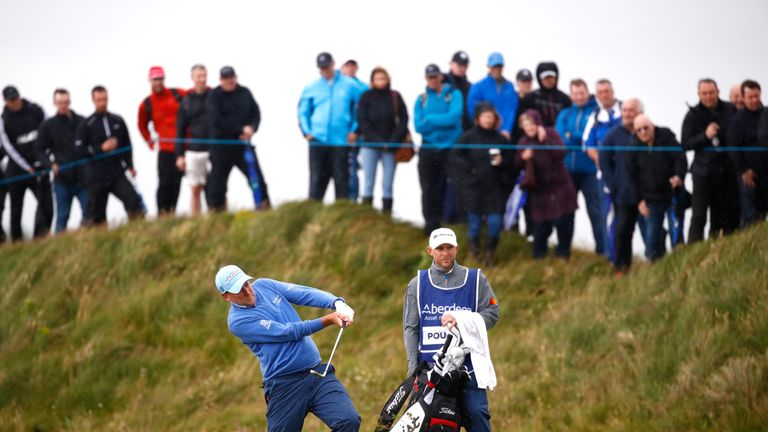 Ian Poulter hits his second shot from the edge of a bunker on the 17th at Dundonald Links