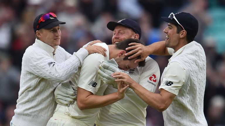 England's Toby Roland-Jones (C) celebrates wicket of South Africa's Hashim Amla for 6 runs with Joe Root (L) and Stuart Broad, 3rd Test, day two, The Oval
