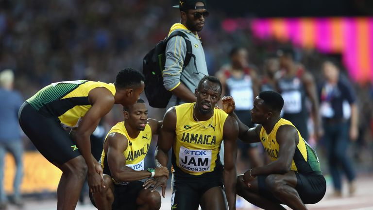 Usain Bolt is helped up by his Jamaican team-mates
