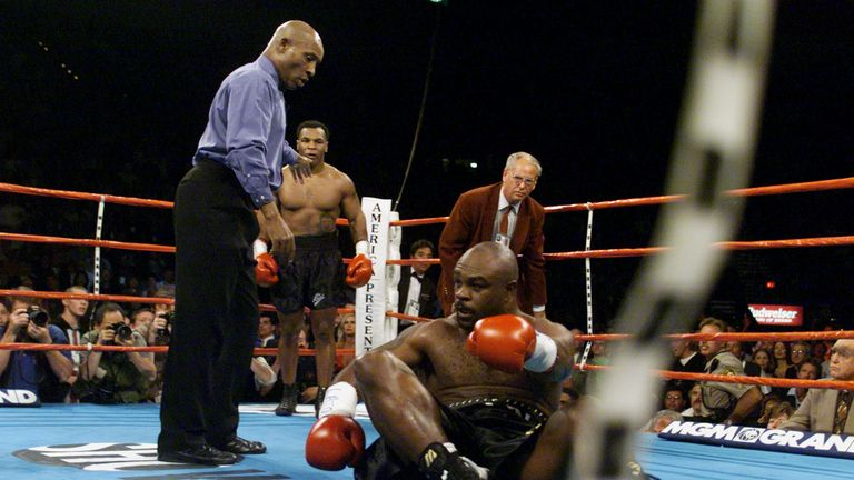 Referee Richard Steele (L) motions Mike Tyson (C) to a neutral corner after he hit Norris after the bell