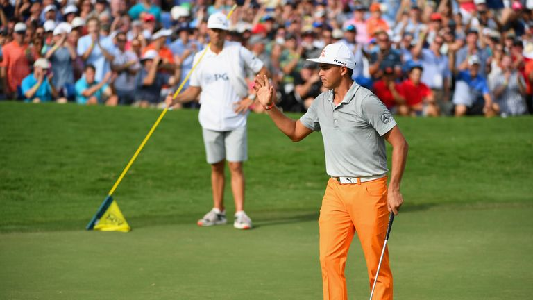 Rickie Fowler acknowledges the crowd after finishing his round on the 18th green