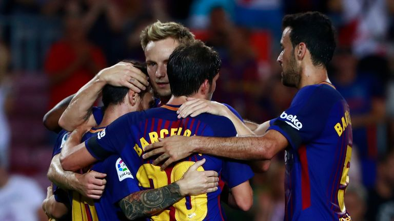BARCELONA, SPAIN - AUGUST 20: Lionel Messi (L) of FC Barcelona celebrates scoring their opening goal with teammates Sergi Roberto (3ndL) Sergio Busquets Bu