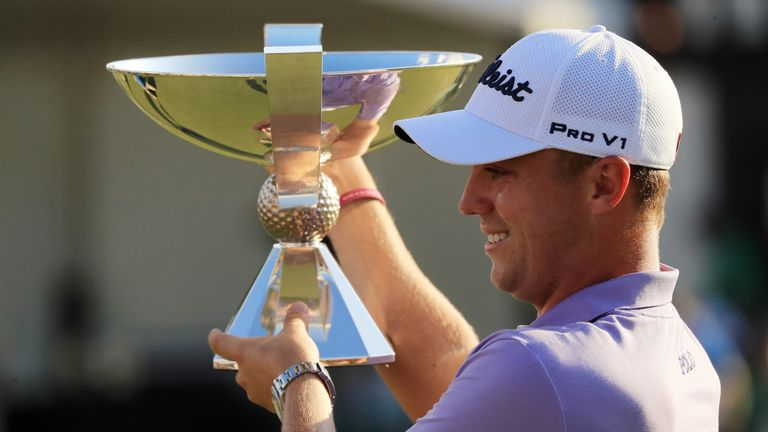 ATLANTA, GA - SEPTEMBER 24:  Justin Thomas of the United States celebrates with the trophy on the 18th green after winning the FedExCup and second in the T