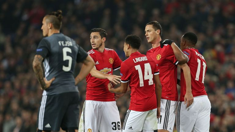 Manchester United players celebrate after taking the lead against Benfica through Mile Svilar's own goal