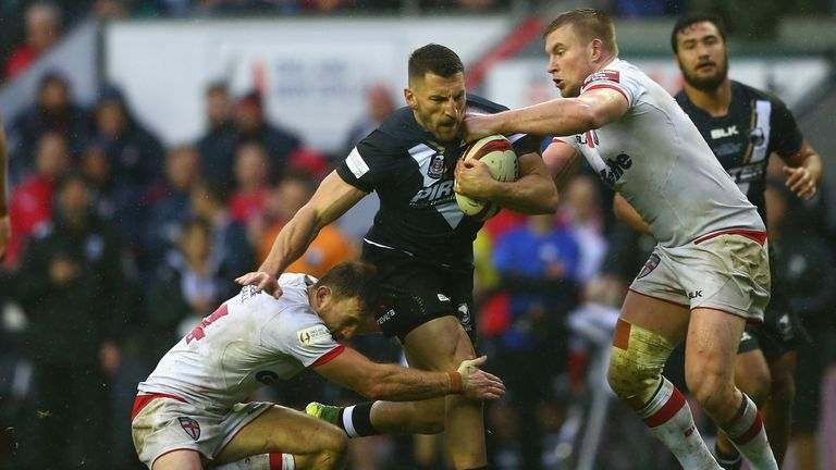 Lewis Brown of New Zealand is tackled by Tom Burgess of England