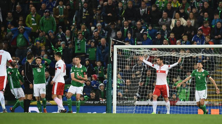 Corry Evans of Northern Ireland concedes a controversial penalty after a handball following a shot from Xherdan Shaqiri.
