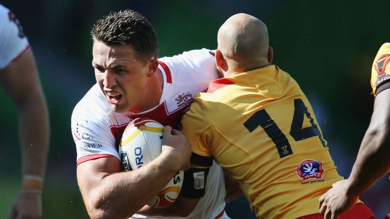 Sam Burgess of England is tackled by Kurt Baptiste of Papua New Guinea