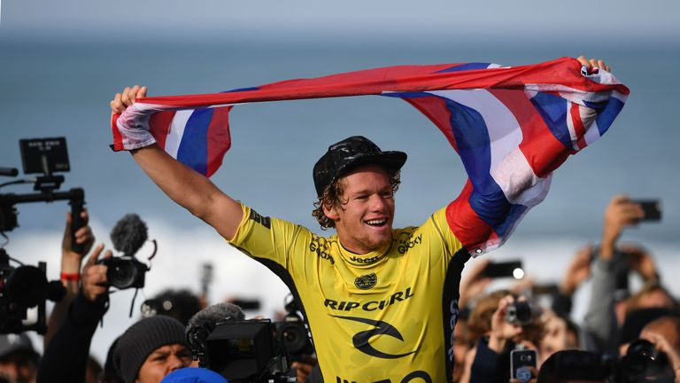 John John Florence waves his country's flag after winning the 2016 World Surf League World Title in Portugal