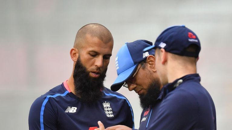 Ali has his finger inspected by bowling coach Saqlain Mushtaq as Mason Crane looks on