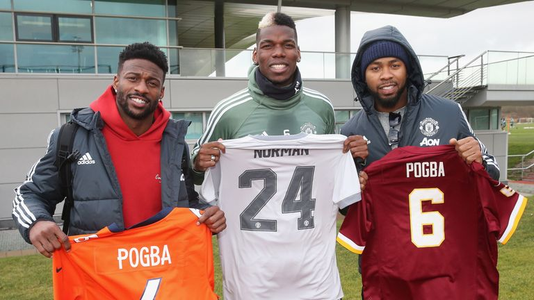 Paul Pogba poses alongside NFL stars Josh Norman and Emmanuel Sanders at Manchester United's Aon Training Complex