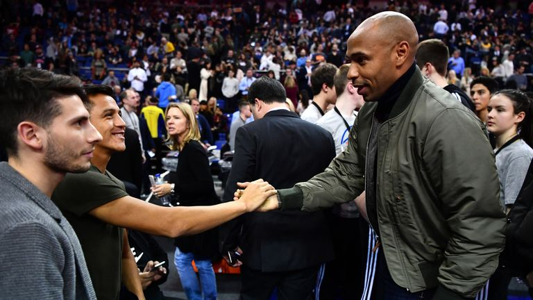 Alexis Sanchez and Thierry Henry shake hands at the NBA match between Indiana Pacers and Denver Nuggets at the O2 Arena last year