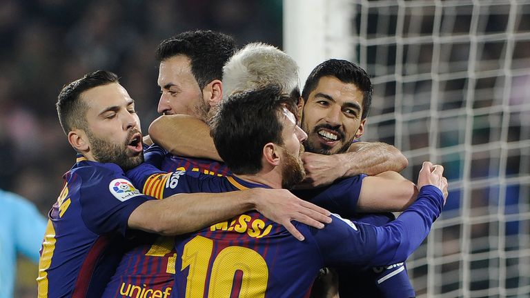 Barcelona's Uruguayan forward Luis Suarez (R) celebrates with teammates after scoring a goal during the Spanish league football match between Real Betis an