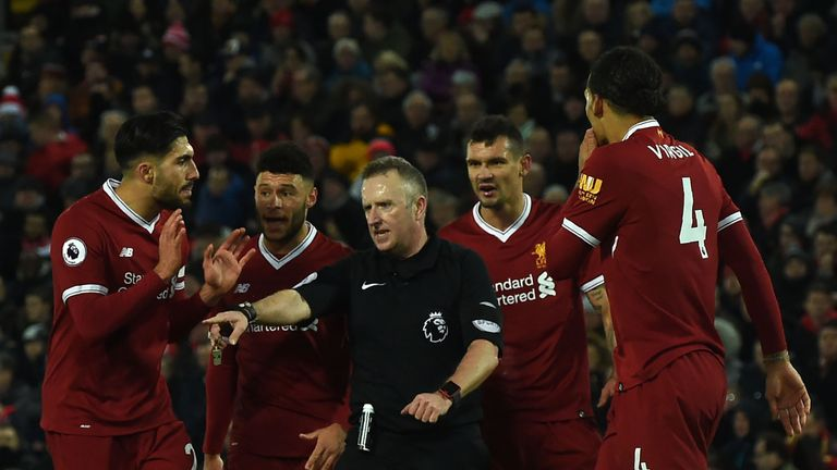 Referee Johnathan Moss (C) awards the first penalty as Liverpool players discuss during the English Premier League football match between Liverpool and Tot