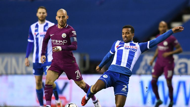 WIGAN, ENGLAND - FEBRUARY 19:  David Silva of Manchester City is tackled by Nathan Byrne of Wigan Athletic during the Emirates FA Cup Fifth Round match bet