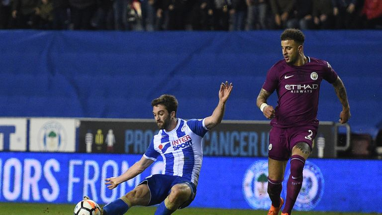 Wigan Athletic's English-born Northern Irish striker Will Grigg (L) scores his team's first goal during the English FA Cup fifth round football match betwe