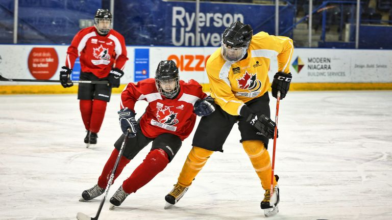 Blind ice hockey players Simon Richard and Vince Ryan vie for possession