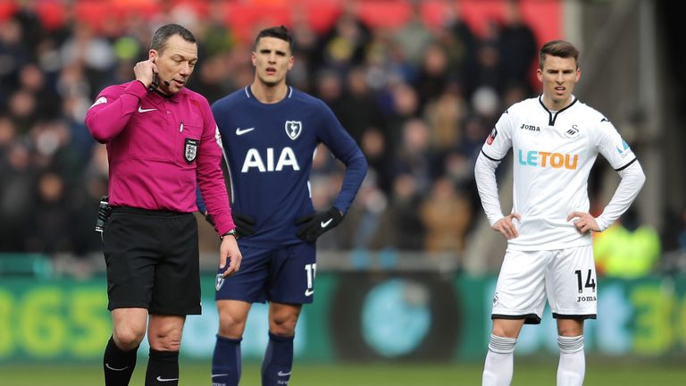 Referee Kevin Friend consults VAR during Tottenham's win at Swansea