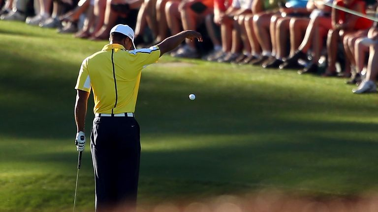 Woods drops his ball after he hit it into the water on the 15th hole during the second round of the 2013 Masters