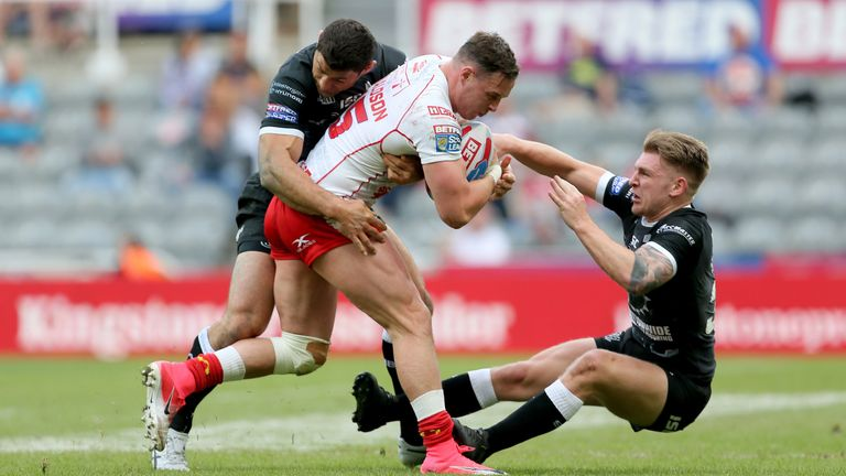 Hull KR's James Donaldson is tackled by Hull FC's Mark Minichiello and Liam Harris