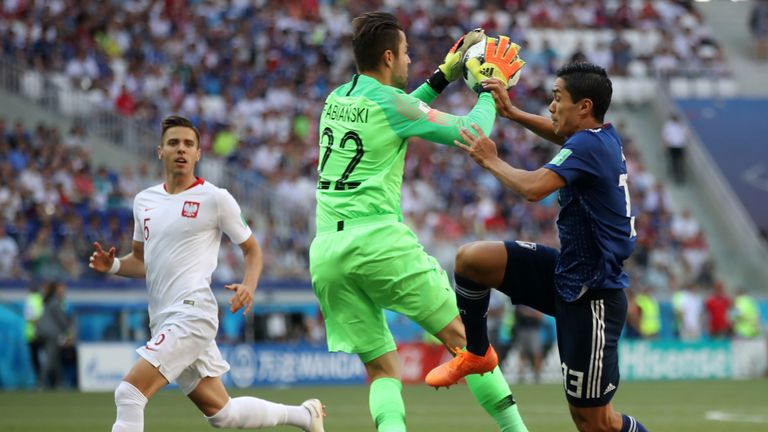Lukasz Fabianski collects the ball under pressure from Yoshinori Muto