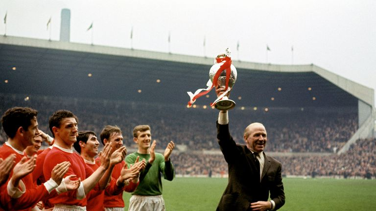 Manchester United manager Matt Busby holds the League Championship trophy aloft as his players applaud