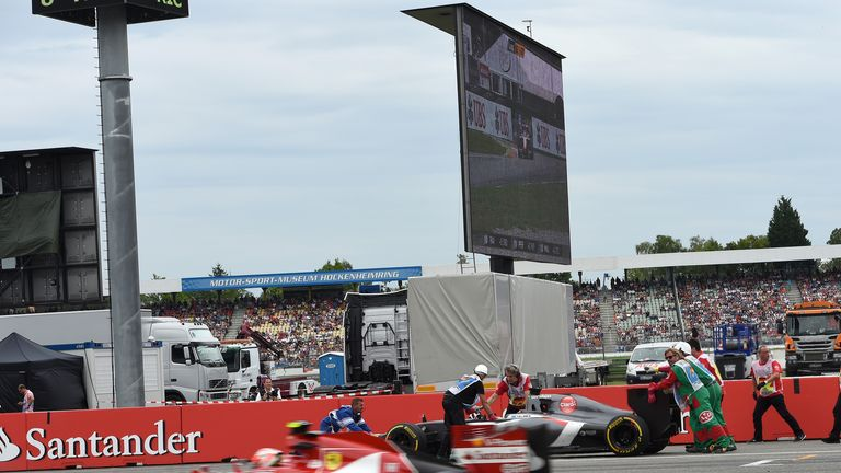Adrian Sutil's car is recovered by the marshals as Kimi Raikkonen flashes past