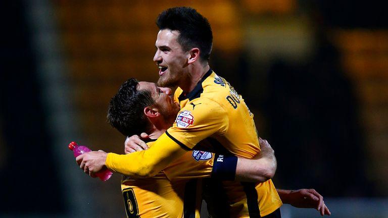 Ryan Donaldson of Cambridge United celebrates with team-mate Tom Champion.