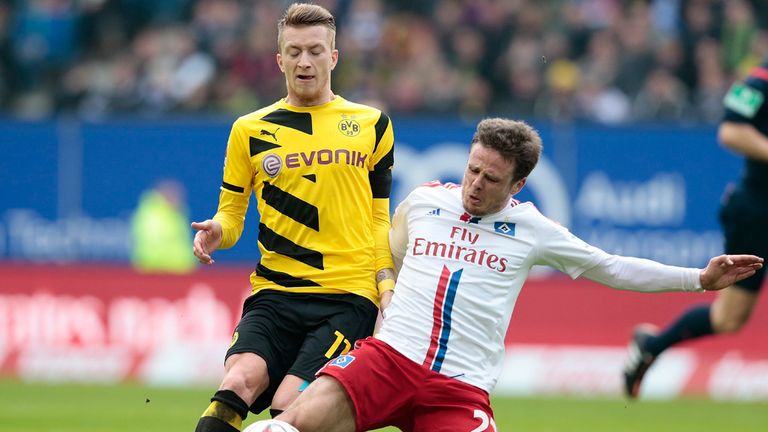 Nicolai Muller of Hamburg angets to the ball in front of Marco Reus