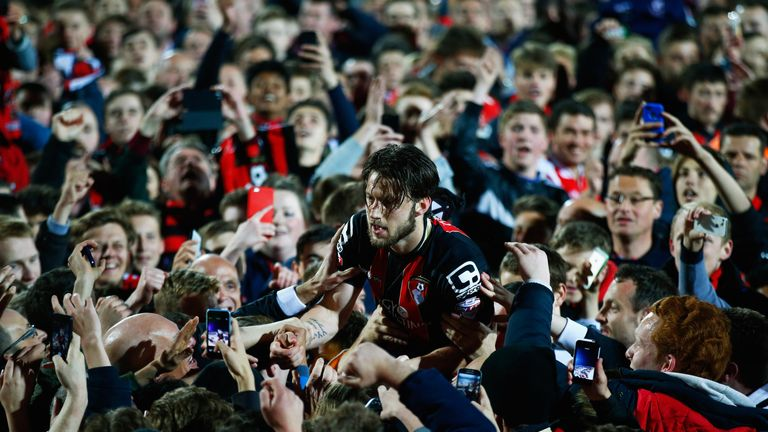 Harry Arter of Bournemouth celebrates victory with fans as they invade the pitch at the final whistle