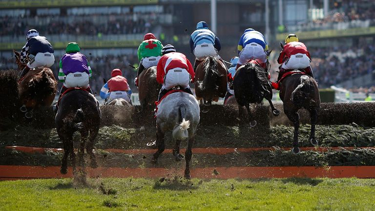 A general view as runners clear a fence at Aintree