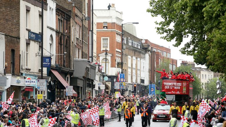Arsenal's victory parade bus makes its way down Upper Street in Islington as fans brave the rain.