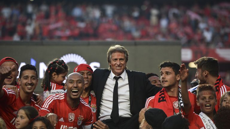 Benfica's players hold their coach Jorge Jesus as they celebrate their 34rd Portuguese league title