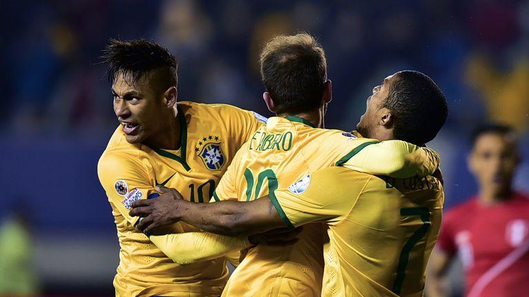 Brazil's midfielder Douglas Costa (right) celebrates with team-mates Neymar (left) and Everton Ribeiro after scoring against Peru.