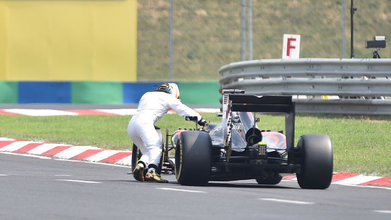 Fernando Alonso pushes his car after stopping on track during qualifying