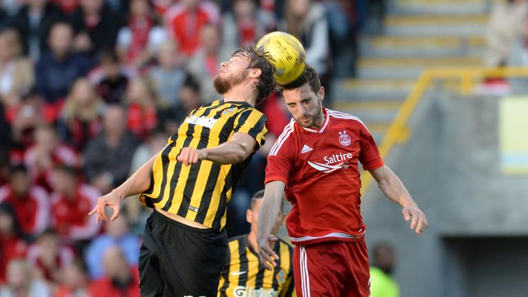 Aberdeen's Greame Shinnie (right) challenges Kairat Almaty's Stanislav Lunin (left) at Pittodrie