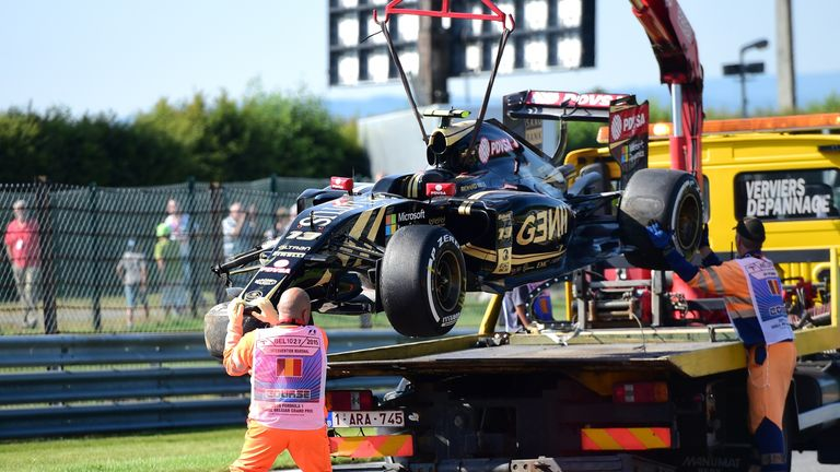 Pastor Maldonado's crashed Lotus is cleared away after crashing at Spa