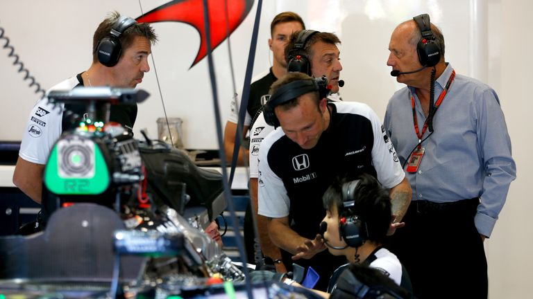 Ron Dennis in the McLaren garage as the engine is worked on
