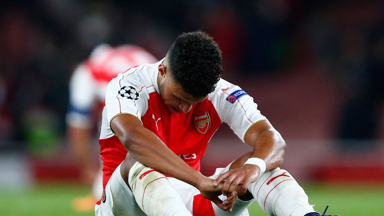 Alex Oxlade-Chamberlain sits on the turf after Arsenal's home defeat to Olympiakos.