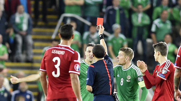 Northern Ireland defender Chris Baird (2nd L) receives a red card from referee Cuneyt Cakir at Windsor Park in Belfast