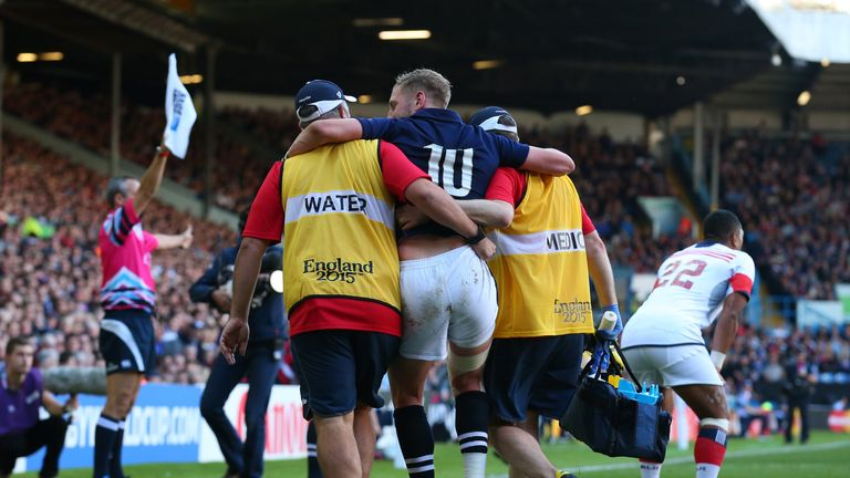 Finn Russell of Scotland leaves the field injured in the second half