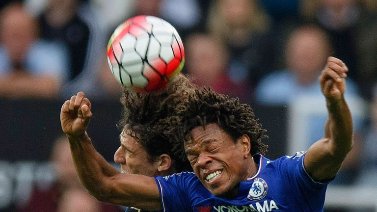Loic Remy and Fabricio Coloccini challenge for the ball