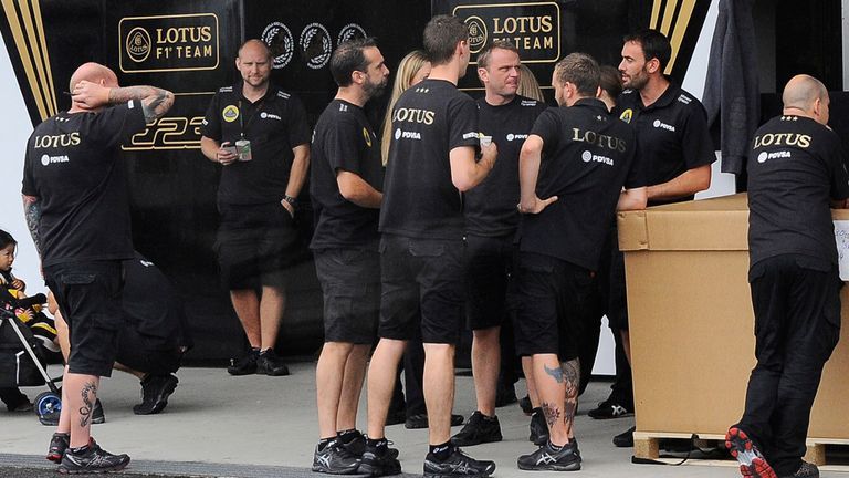 The Lotus team wait outside their closed garage in the Suzuka paddock