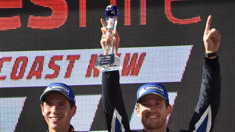 Sebastien Ogier (R) and his co-driver Julien Ingrassia (L) celebrate after winning their third World Rally Championship